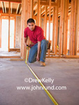 Picture of a construction worker using his measuring tape in a new home under construction.  The worker has on a red shirt and blue jeans. Advertising pictures for new construction and home builders. Mexican worker pics.