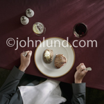 Looking down on meat and potatoes on a fine china plate with a man's hands on either side holding a knife and fork.