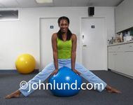 Colorful ad picture of an attractive black woman in a green top and powder blue pants sitting on a blue exercise ball in the exercise room. Shoulder length black hair and smiling at the camera as she straddles the exercise ball. Healthy living.