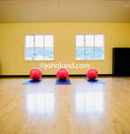 Health Club or Spa photo of three exercise medicine balls on mats in a large empty work out room. The three medicine balls are resting on exercise mats in front of a large yellow wall and two windows.