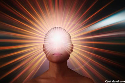 An Asian woman is seen in a serene state of meditation as her third eye radiates light rays in this new age stock photo. Streaks of light representing an aura on a black background.