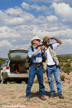 Black man and white man wearing hats looking into the distance with a car in the background and cloudy sky. The seniors are wearing blue jeans. The Caucasian man has on a blue work shirt and a cowboy hat.