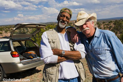 Two senior men standing in the desert on roadside near their car. One man is black with a gray beard, the other man is white with a gray mustache and hair. The white guy is wearing a old cowboy hat.