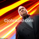 Stock photo looking up at a menacing bouncer with a scowl on his face and a shaved head. He is wearing a sports coat. Picture of a mean looking disco club bouncer.