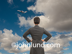 A woman executive looks off into the sky at a business jet climbing through the clouds in an image about missed opportunities, travel challenges and business meeting issues.