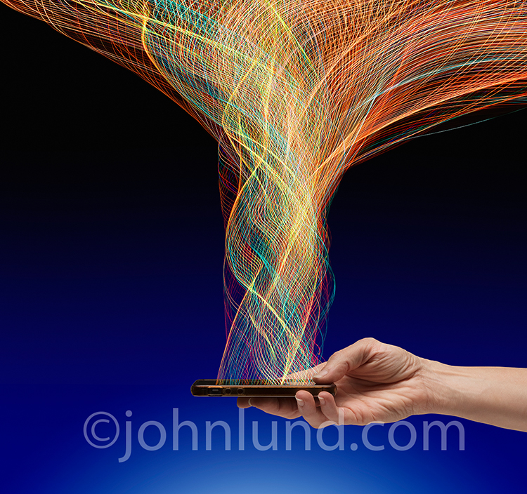 Mobile connections and networking are vividly portrayed in this stock photo of a hand holding a cell phone from which a complex and intricate web of light trails, representing data transmission, is expanding outwards.