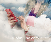 A mobile phone is being used in the cloud, literally, in this stock photo digital composite and photo montage of a woman using her smart phone while multiple-exposed with a cloudscape.