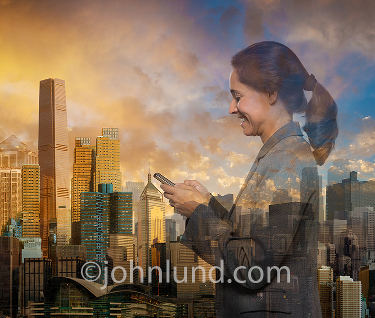 A smiling and successful businesswoman is multiple-exposed over a futuristic cityscape in a stock photo about mobile connections, networking and business success.