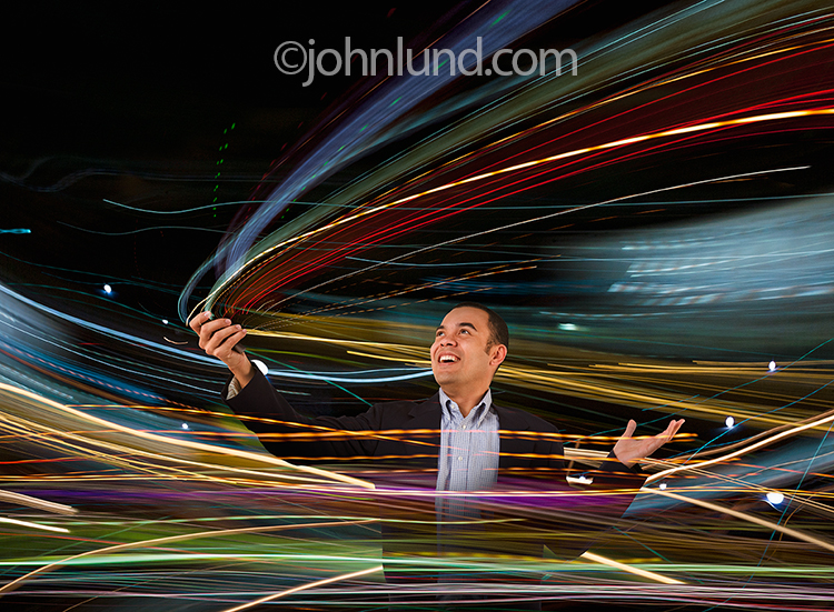 A businessman happily watches data stream from his mobile device as he is surrounded and enveloped in the wireless transmission of information seen in the form of streaks of colored lights,the product of new communications technology.