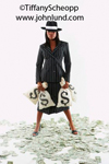 A woman dressed like a gangster from the 20's in a fedora and pin striped suit is standing with legs spread apart and holding four big bags of money. She has a defiant look to her.