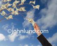 Picture of a womans arm and hand reaching up and plucking a dollar bill off of the branch of a money tree growing cash and currency. Blue sky background. Money and currency photos for ads.