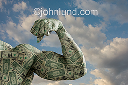 The power and strength of money, cash and dollars are illustrated in this stock photo of a bulging bicept created from money against a lightly clouded sky background.