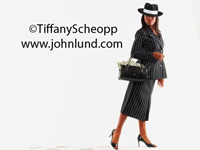 An African american woman standing against a white background holding a purse in the crook of her arm. Her purse is overflowing with money,dollars, greenbacks. The woman is wearing fedora with a white band.