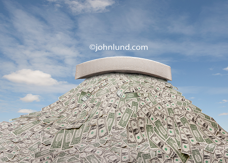 A mattress sits high upon a huge mound of money in a humorous stock photo about savings and investment.
