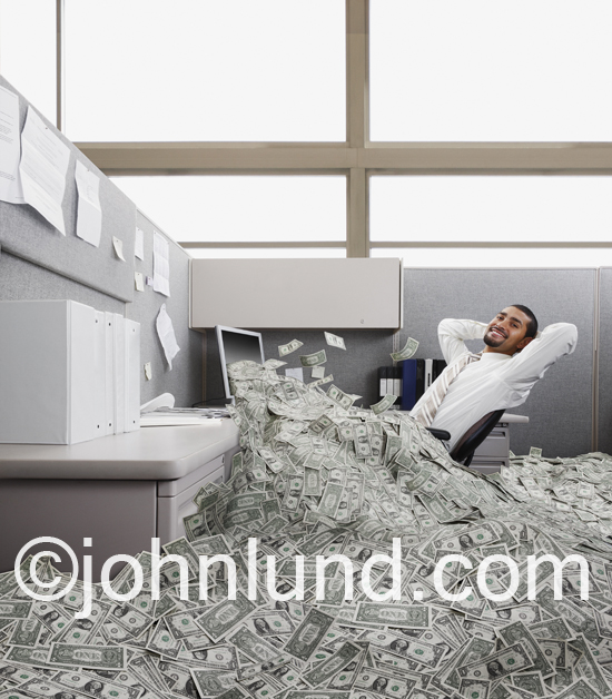 Businessman leans back in his office chair while cash pours out of his monitor filling up his cubicle with dollars.