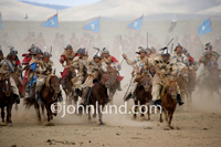 The Mongolian Hordes of Genghis Khan charge across the plain on horseback in a re-enactment of a battle celebration Genghis Khan's Birthday.