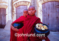 Two young monks hold alms bowls in this Burmese temple complex. Every morning the monks make their rounds and receive rice and other foodstuffs. They then return to their temple and eat.