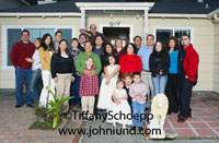 Lifstyle and leisure picture of a huge Mexican or Latino family posing for a family foto outside the family home.  There  are grandparents, parents kids youngsters toddlers and a lion statue.  Mexican Family Pics.