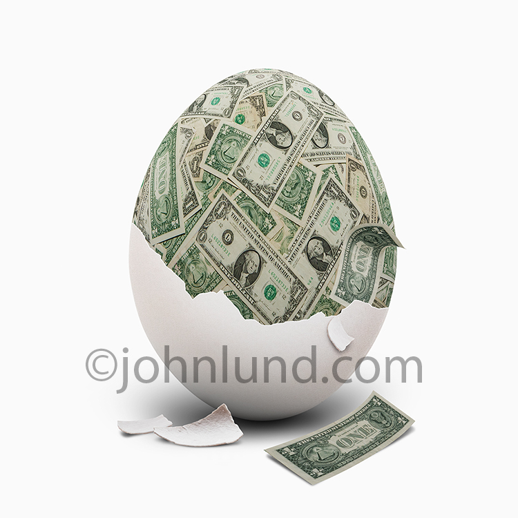 An egg with it's shell peel away reveals an interior of money, dollar bills, in a stock photo about retirement nest eggs, financial planning and personal savings.