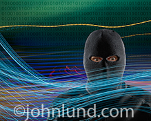 A network hacker is vividly seen in this image that combines elements of streaking lights (representing streaming data), binary numbers, and a menacing figure wearing a ski mask.