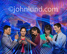 A networking business team, five people use their mobile devices to stay connected in a stock photo about wireless technology, future communications, and networking connections.