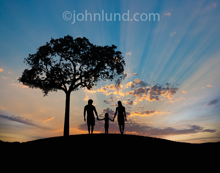 This story book happy family features a mother, father and daughter holding hands and walking silhouetted into a sunrise in a metaphor for new beginnings and happy times ahead.