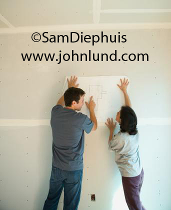 Pictures of a couple building their own home. The couple is holding up the blueprints against the freshly sheet rocked walls. Photo of a new homeowner couple with blue prints in their home still under construction.