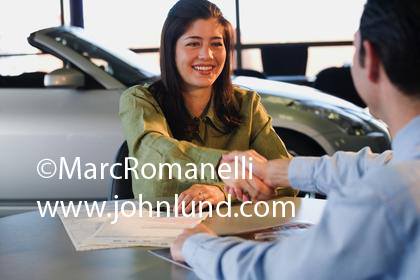 Woman shaking hands with a new car salesman in the showroom. They are seated at his desk and he has just sold her a new car. Sealing the deal.  Made the sale.