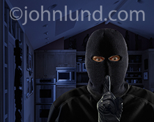 A burglar, wearing a ski mask and gloves, holds his finger up to his lips in a gesture of silence as he stands in a darkened kitchen at night in an image about home security issues.