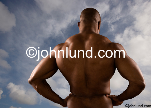 Nude study of a massively muscled African American body builder's back shot against a cloudy sky.
