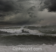 Dark clouds roll over rough seas and tossing waves in this stock photo of an ocean storm.