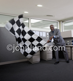 A senior executive waves a checkered flag in an office indicating a successful business milestone...and winning!