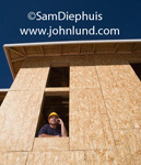 Constructon picture for advertising - Contractor in a second story window of an unfinished building under construction talking on his cell phone and wearing a yellow hard hat. Pic taken from far below the man. Blue sky background.