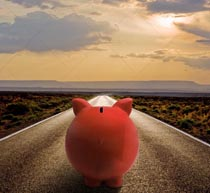 A piggy bank is on the road to financial success in this stock photo featuring a piggy bank looking down a long, deserted highway.