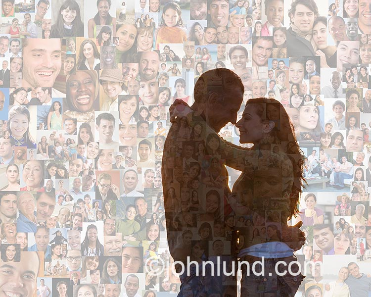 This online dating and romance photo shows a couple gazing into each other's eyes in an embrace against a backdrop of hundreds of individual portraits with the clear inference of social media and networking.