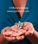 Classic origami crane made from a dollar bill is perched in a woman's hand.  The woman has both hands facing up, one under the other. She is wearing blue dress. Closeup of woman's hands.