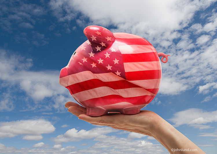 A patriotic piggy bank, held aloft against a blue sky, has the American flag superimposed upon it in a stock photo about investing in America.