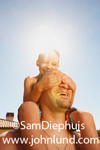 A young boy is perched upon his dads shoulders, and he has his hands over his fathers eyes presumably playing a form of peek-a-boo.  Bright sun in sky above boy's head. Clear blue sky. Summer fun for dads and their kids.