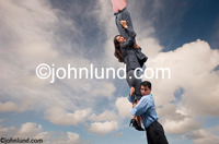 Pictures of funny looking business people as they hang desperately on to each other, in the sky, for support. Picture of business men and women being silly hanging from the sky