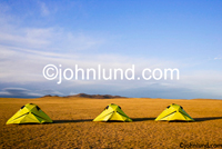 Three tents lined up on a barren landscape in Mongolia: Adventure travel and vacations. Pictures of tents in Mongolia.  The tents are bright yellow on a barren brown dirt landscape against a brilliant blue sky.