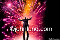 A conductor orchestrates fireworks in a concept stock photo showing leadership, possibilities, energy, vitality and accomplishment.