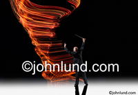 A conductor, baton in hand, orchestrates swirling light patterns of energy and vitality in this stunning stock photo.