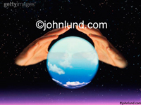 Stock photo of a pair of hands floating over a crystal ball with the sky and clouds visible inside the ball where the future is hidden.