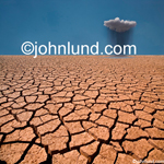 Stock photo of Global warming: a dry cracked desert with a solitary cloud dropping rain onto the parched earth in the distance.