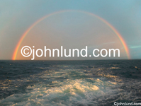 Stock shot of a full rainbow over the ocean in the wake of the boat as the late afternoon sun skims over the water.  Rainbow pics.
