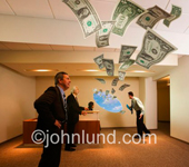 In this stock image about cash flow dollars fly through the office from a hole in the wall. People in the office are watching the money fly by in amazement. Fabulous flying money photos. CEO bonuses.