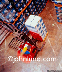 Overhead view of a forklift in movement carrying a pallet load of boxes and products across the concrete floor of a warehouse.