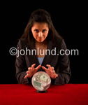 Picture of an ethnic woman with a crystal ball and money floating inside as she tells the fortune of investment strategies.