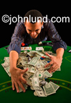 Stock picture of an African American man pulling in gambling winnings (the pot) with his hands. The pot is full of cash, money, and jewelry.