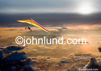 Photo of a hang glider soaring high above the clouds in a symbolic Metaphor of freedom, adventure and exploration. Picture of a hanglider.